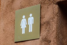 A sign for a washroom with a man and woman on it